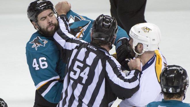 Sharks defenseman Roman Polak (46) is separated from Predators defenseman Barret Jackman by NHL linesman Greg Devorski (54) in the third period Saturday.
