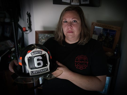 Kate Maxwell, girlfriend of Lt. Christopher Leach who died last year in the fatal Canby Park fire, holds a helmet with his station number on it.