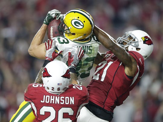 Green Bay Packers receiver Jeff Janis (83) catches a Hail Mary against Arizona Cardinals' Patrick Peterson (21) and Rashad Johnson (26) at the end of the fourth quarter during their NFC divisional playoff game at University of Phoenix Stadium.