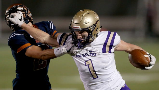 Notre Dame Prep's Jake Smith (1) fights his way out of the grip of Cienega's Diego Rubi (2) on a third quarter run in the state 5A semifinal at Mountain View High School, Friday November 17, 2017, Tucson, Ariz.