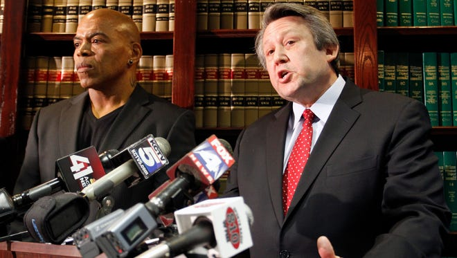 Attorney Ken McClain, right, with former Kansas City Chiefs linebacker Chris Martin,  talks about a lawsuit filed earlier in December against the team. There are now 14 plaintiffs.