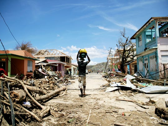 A man walks amid destruction on a street Sept. 23, 2017, in Roseau on the Caribbean island of Dominica following passage of Hurricane Maria.
