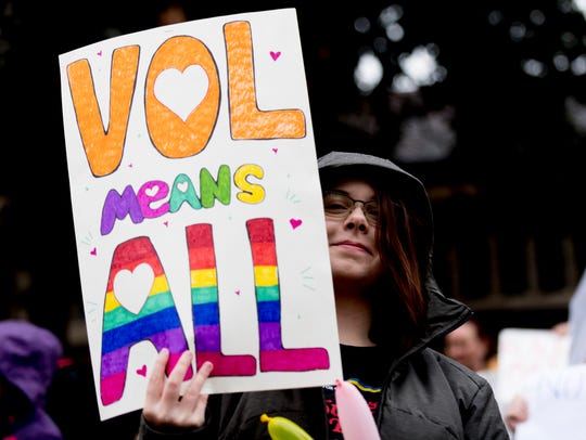 Hannah Maddos, UT freshman, holds a sign during a protest