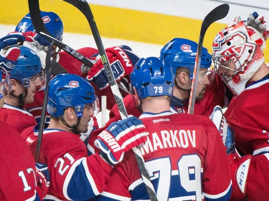 Players from the Montreal Canadiens celebrate after defeating the Tampa Bay Lightning following Stanley Cup hockey playoff game in Montreal, Sunday, April 20, 2014. (AP Photo/The Canadian Press, Graham Hughes)