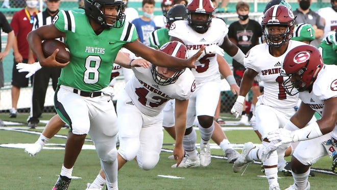 Van Buren quarterback Gary Phillips looks for running room on the outside of the Springdale rush, Friday, August 28, during first quarter play at Blakemore Field.