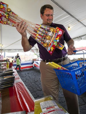 Alan Garri of Ocala is shown in this file photo as he fills his basket with fireworks in 2019. With the cancellation of multiple July 4th events in Marion County due to the COVID-19 pandemic,  fireworks tents may get even busier this year.