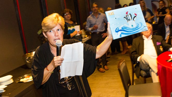 Executive director Julie Schnieder begins the live auction of the childrens' artwork.