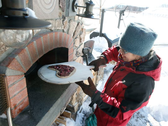 Reporter Karen Miltner places a Nutella, Dark Chocolate and Blood Orange Pizza in a wood-fired oven at her home in Geneva.