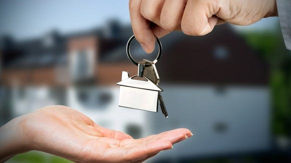 A person handing house keys to another person