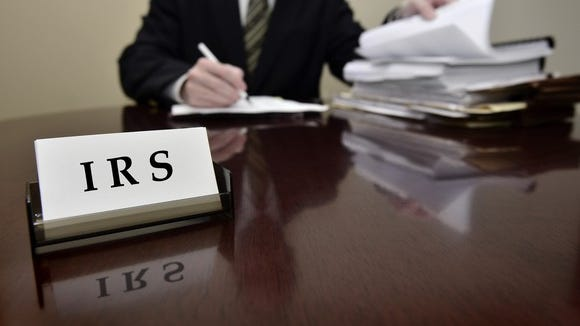 An IRS agent examining paper tax filings at his desk.