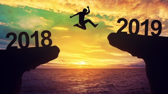 Person jumping over an ocean at sunset between two cliffs, one with numbers 2018 and the other with 2019.