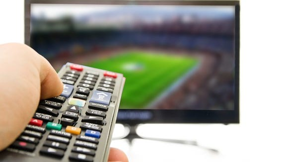 A person points a remote control at a TV.
