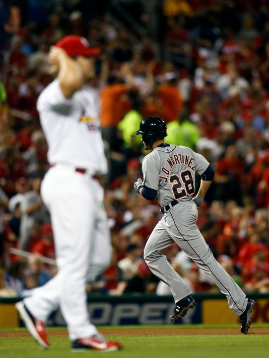 Detroit Tigers' J.D. Martinez rounds the bases after hitting a solo home run off of St. Louis Cardinals relief pitcher Mitch Harris, left, during the seventh inning of a baseball game Friday, May 15, 2015, in St. Louis. (AP Photo/Scott Kane)
