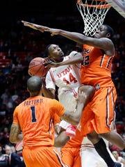 Utah forward Dakarai Tucker, center, goes to the basket