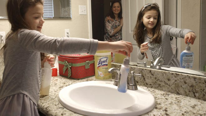 Lily Cherry, 8, cleans her bathroom as her mother, Andrea, supervises at their home in Kingwood, Texas. Andrea Cherry believes chores give her children a sense of family responsibility.