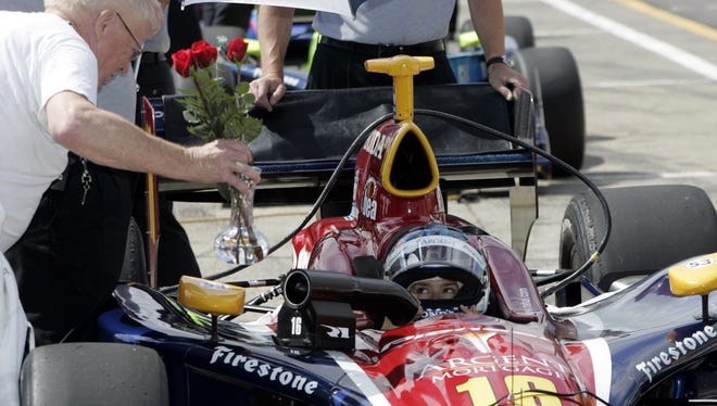 Dale Campfield, left, delivers roses to Indy Race car driver Danica Patrick on pit road during an open test session at Watkins Glen International in 2005. Campfield said he wanted to treat her like a lady. A crew member accepted the flowers for Patrick, who was in the middle of practice.