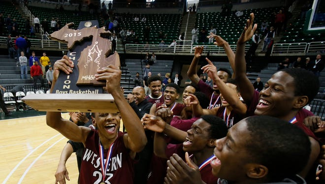 Detroit Western Josh McFolley holds the championship trophy as they celebrate after their 62-59 win overSaginaw Arthur Hill in the  MHSAA Boys Class A final basketball game on Saturday, March 28, 2015 in East Lansing.