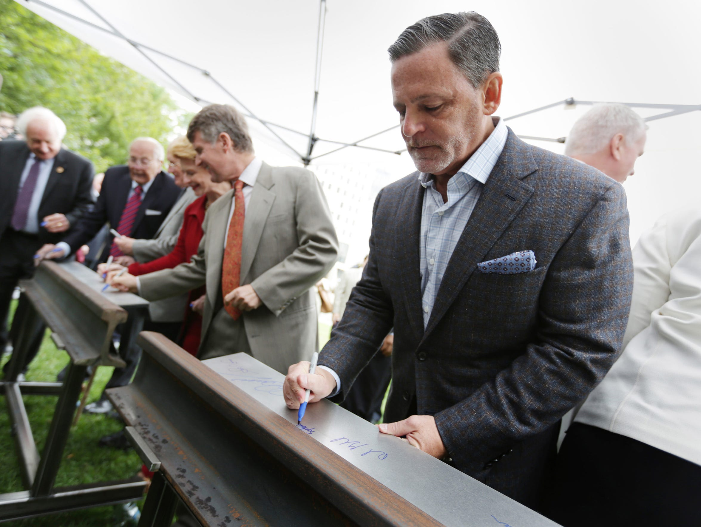 Dan Gilbert, right signs a rail during a Ceremony to
