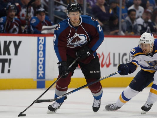 Colorado Avalanche center Nathan MacKinnon, left, looks to pass the puck as St. Louis Blues left wing Jaden Schwartz defends in the second period of an NHL hockey game, Sunday, March 5, 2017, in Denver. (AP Photo/David Zalubowski)