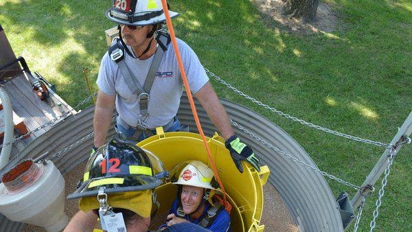 A Nationwide Insurance publicity photo illustrates firefighters using the  grain bin rescue tube and auger.