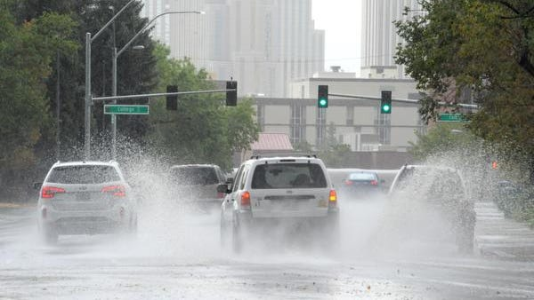 Cars navigate through ponding water across Virginia Street near UNR on Monday afternoon.