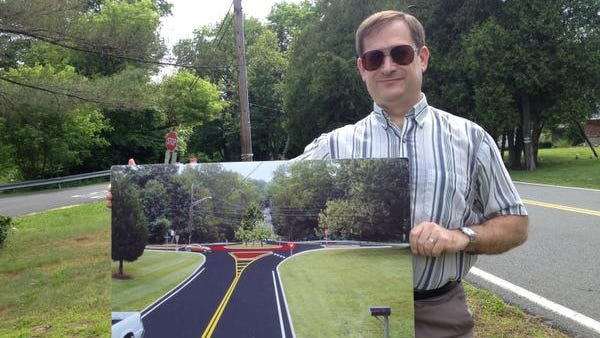Wesley Hills Mayor David Goldsmith, photographer June 17, 2014, holds up a rendering of a roundabout coming to the intersection of Forshay and Willow Tree roads. The project is part of a larger construction job that is expected to begin later this year and finish in 2016.