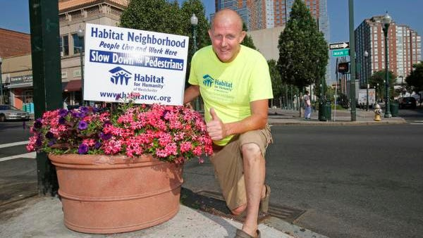 "Jim Killoran, head of Habitat for Humanity of Westchester, has begun his own personal ""traffic-calming program,"" and installed signs in New Rochelle, Mount Vernon and Yonkers asking motorists to drive carefully. Killoran is photographed at one of the signs July 2 on Main Street in New Rochelle."