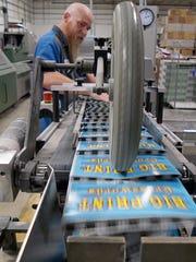 Ernie Sanders works on binder machine Monday afternoon