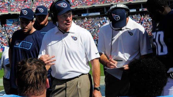 Titans head coach Ken Whisenhunt talks with his players on the sideline during the first quarter against the Texans at LP Field Sunday Oct. 26, 2014, in Nashville, Tenn.