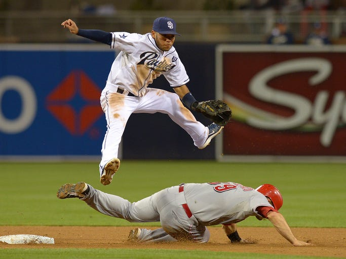 San Diego Padres third baseman Alexi Amarista (5) leaps over Cincinnati Reds catcher Devin Mesoraco (39) after forcing him out and throwing to first during the sixth inning at Petco Park. The runner was safe at first.