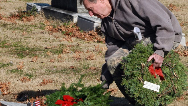 Wayne Baker lays a wreath on the grave of a Veteran at the Gallatin City Cemetery on Sat. Dec. 16, 2017.