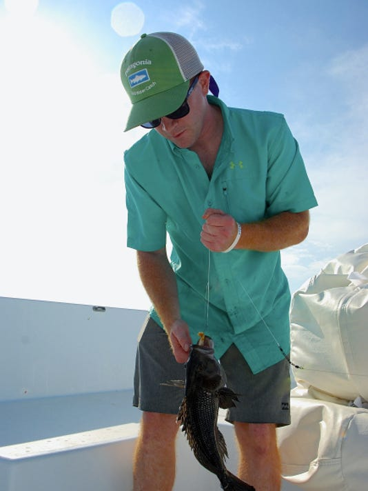The author's brother-in-law, Casey McGarvey, hauls in one of many black sea bass into the boat during a fishing trip to the Long Island Sound.