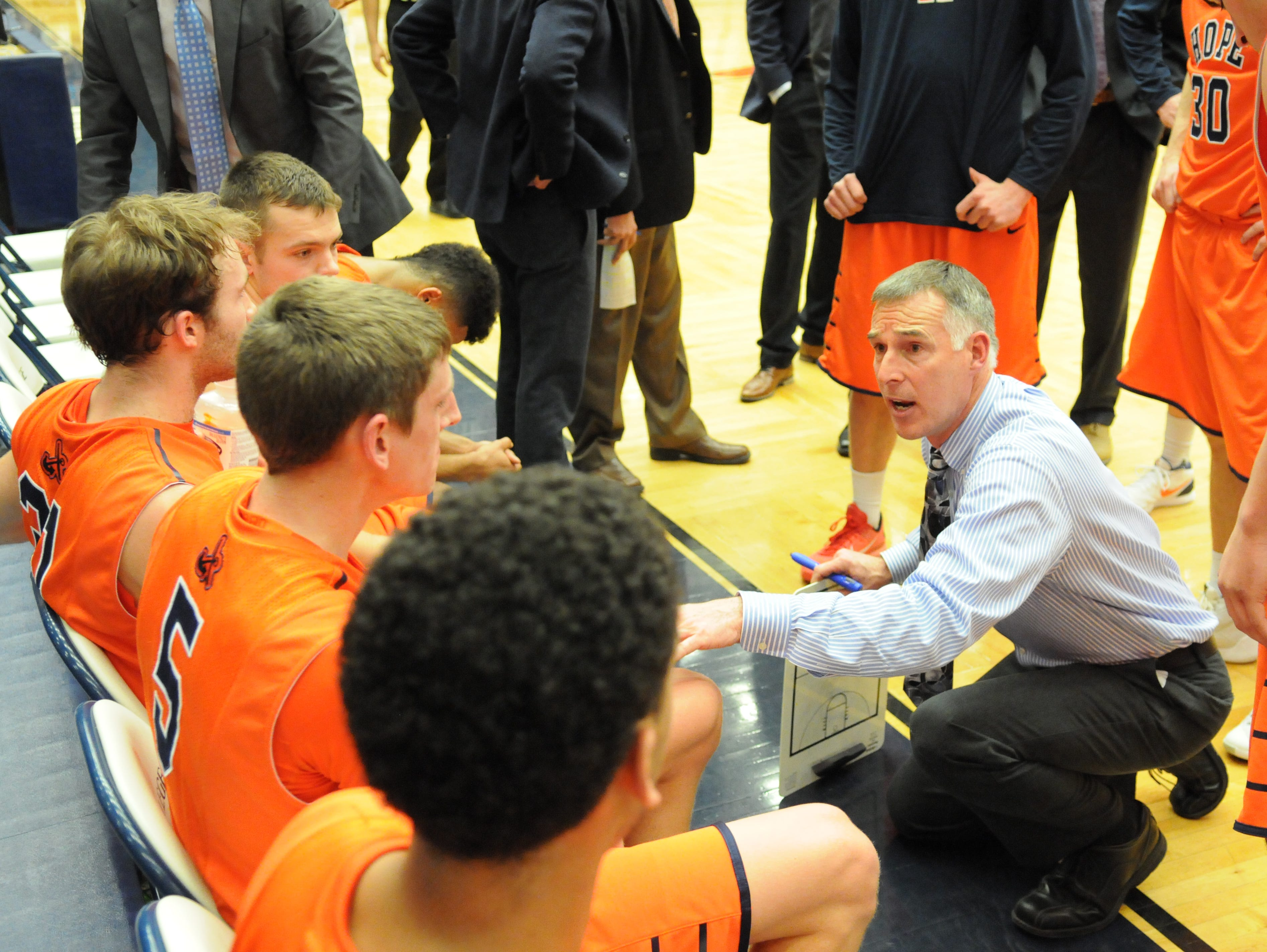 Third-year Hope College basketball coach Greg Mitchell talks with his team during a timeout.