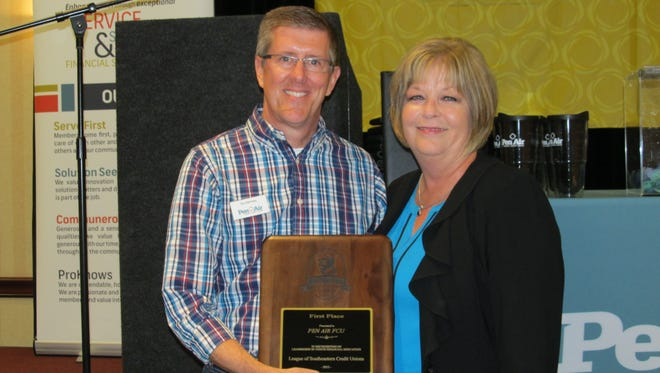 Stu Ramsey, president/CEO of Pen Air Federal Credit Union, receives the first place Desjardins Youth Financial Education Award from Judy Scott, Member Relations Consultant for LSCU.