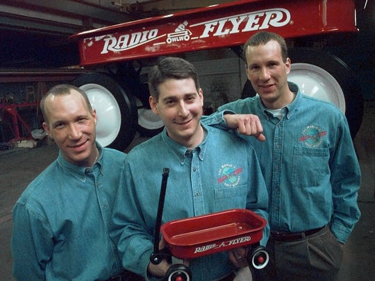 The Pasin brothers, from left: Antonio, Robert, and Paul, shown in 1997, are the third generation of Pasins producing the classic Radio Flyer wagon in their Chicago factory. Robert holds a small version of their classic wagon with the world's largest red wagon behind them.