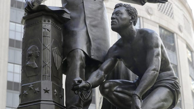 A detail of a statue that depicts a freed slave kneeling at Abraham Lincoln's feet rests on a pedestal, Thursday, June 25, 2020, in Boston. The statue in Boston is a copy of the Emancipation Memorial, also known as the Emancipation Group and the Freedman's Memorial, that was erected in Lincoln Park, in Washington, D.C., in 1876. Three years later, the copy was installed in Boston. Calls are mounting for the removal of both statues.