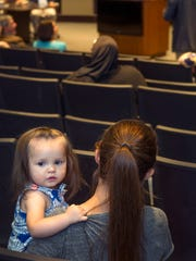 Renae Sanchez, right, and her 15-month-old daughter, Faith, listen to remarks at a town hall meeting Thursday, April 20, 2017, at Las Cruces City Hall. Sanchez's son Arron is enrolled in kindergarten and she said she was there because she is concerned about her children's education.