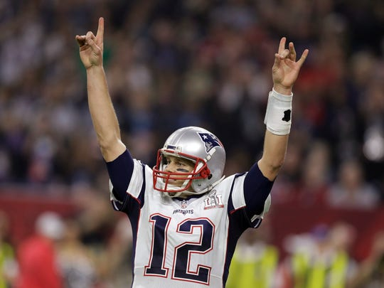 Quarterback Tom Brady raises his arms after the New England Patriots scored a touchdown during overtime of Super Bowl 51 against the Atlanta Falcons on Sunday.