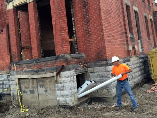 A construction worker moves pvc tubing into a basement window of the Ransom Gillis House in the historic neighborhood of Brush Park in Detroit, Tuesday, July 21, 2015.
