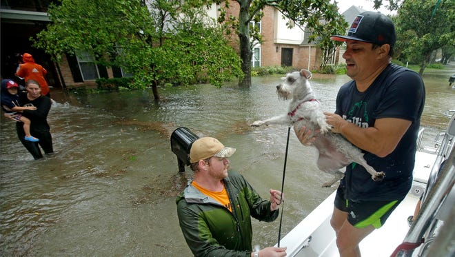 Volunteers evacuate people and pets from a neighborhood inundated by floodwaters from Tropical Storm Harvey on Aug. 28 in Houston, Texas. An Empty the Shelters event is set for Saturday at the Dutchess County ASPCA to make room for pets impacted by the hurricanes in the south.