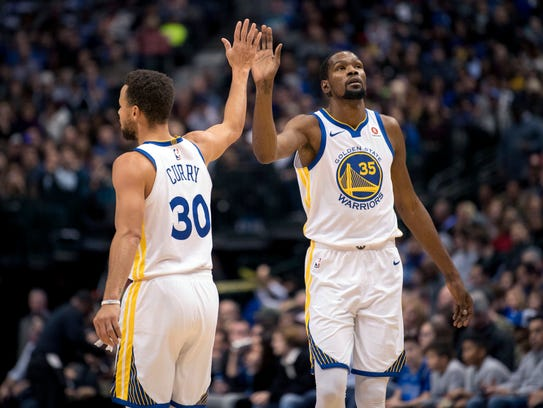 Stephen Curry and Kevin Durant celebrate during a game