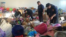 Juárez firefighters go through the bags of donated toys received last year. The annual Santa Bombero toy distribution campaign is Thursday.