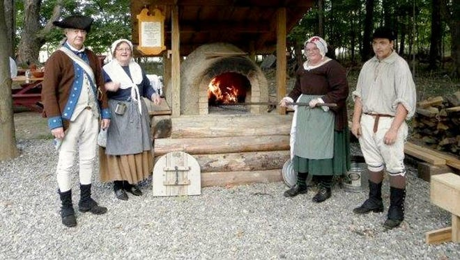 Friends of the Fishkill Supply Depot members Jim Burr Sr., Judy Wolf, Tracy Wolf and Jim Burr Jr. stand in front of the working Colonial clay oven. Vistors will get to taste handmade freshly baked breads and pies all weekend.