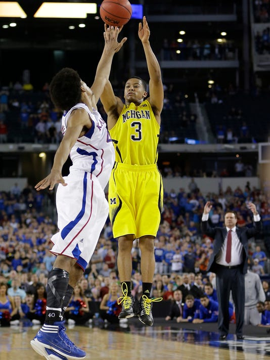 FILE - This March 29, 2013 file photo shows Michigan's Trey Burke (3) making a three-point basket in the final seconds of the second half of a regional semifinal game against Kansas in the NCAA college basketball tournament in Arlington, Texas. Michigan freshman Jordan Poole's buzzer beater, which gave the Wolverines a 64-63 victory and set up Thursday's matchup with Texas A&M in Los Angeles, is drawing comparisons to Burke's shot against Kansas in the 2013 regional semifinals. (AP Photo/David J. Phillip, file)