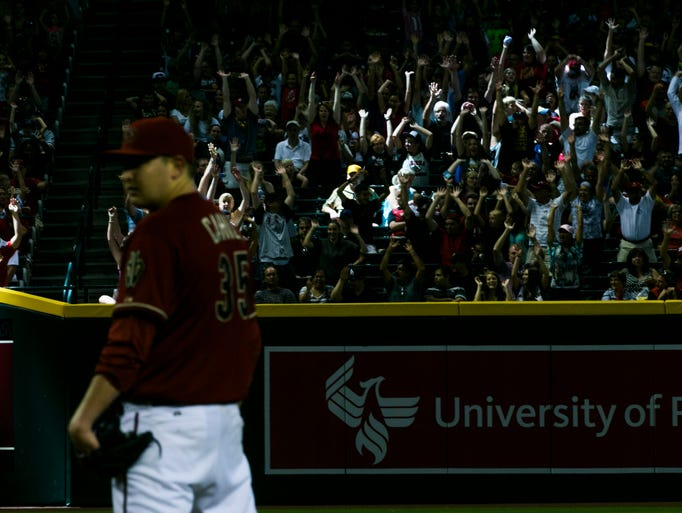 Fans perform the wave as Diamondacks' Trevor Cahill prepares to pitch against the Pirates at Chase Field  on Sunday, August 3, 2014, in Phoenix.