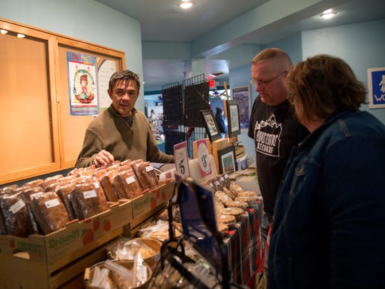 Jerry Benally, left, owner of the From Scratch Bakery by the Dough Boys, talks to customers Linda Windham and her son Mat Windham Friday during the Shiprock Chapter Christmas Bazaar at the Shiprock Chapter House.
