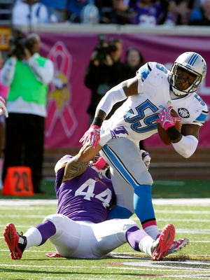 Detroit Lions outside linebacker Tahir Whitehead (59) is stopped by Minnesota Vikings running back Matt Asiata (44) after intercepting the pass intended for Asiata during the first half of an NFL football game Sunday, Oct. 12, 2014, in Minneapolis.