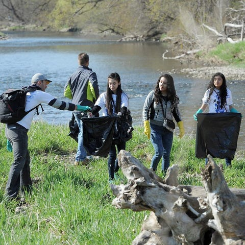 Griffin Knipp (left) picks up trash with a group...