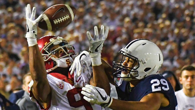 USC wide receiver JuJu Smith-Schuster, left, catches a pass under tight coverage from Penn State cornerback John Reid during the Rose Bowl in Pasadena, Calif. Penn State lost the back-and-forth contest, 52-49.