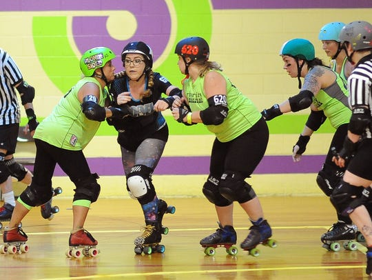 SODEL's Caitlyn Short, also known as Brute E. Licious, tries to break through a block by River City team members Amy Burks, aka Blondsided, (left) and Candice Gentry, aka Otter Chaos.